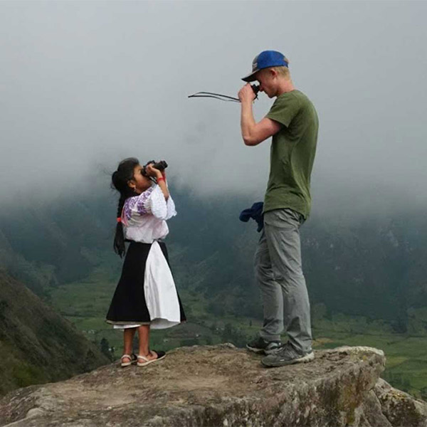 A student with a local inhabitant standing upon a mountain looking at each other with binoculars.