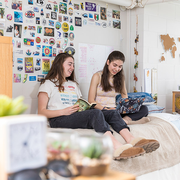 Two students in a residence hall room.