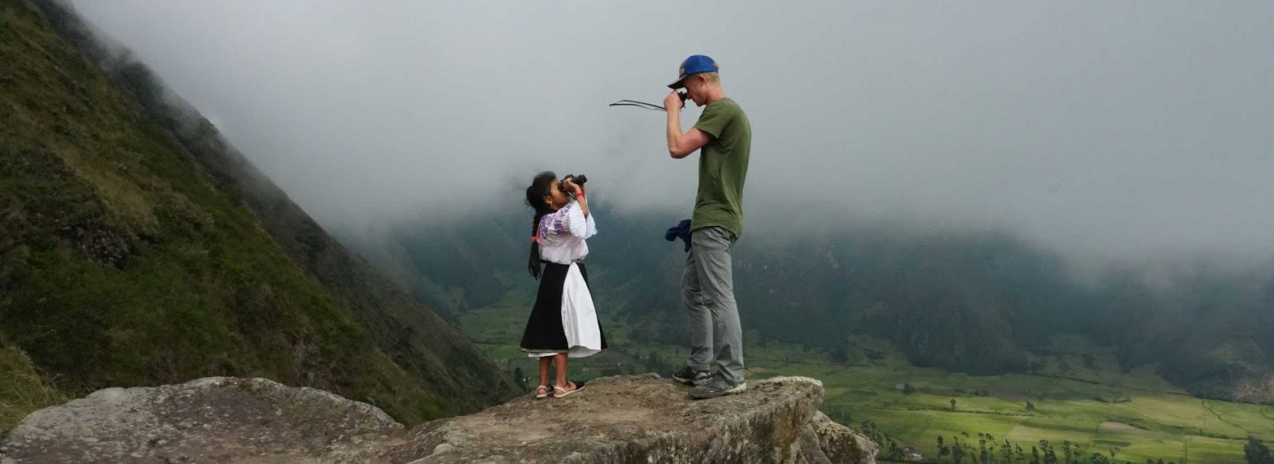 A student and a local inhabitant stare at each other with binoculars while standing atop a mountain.